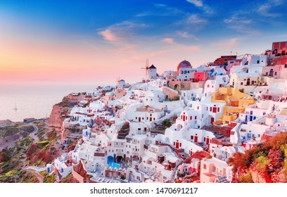 Greece, Santorini island. Charming view of Oia village, traditional Greek white houses and mill at amazing dramatic sunset sky. Oia (Ia) on Santorini is famous and popular travel destination in Europe