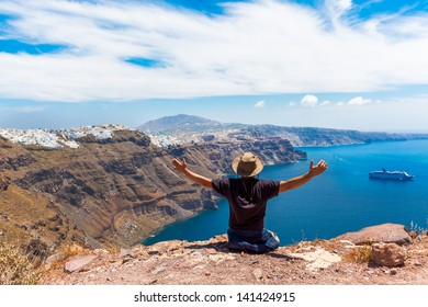 Greece Santorini island in Cyclades, tourist traveler enjoyng the amazing view with awe with hands open