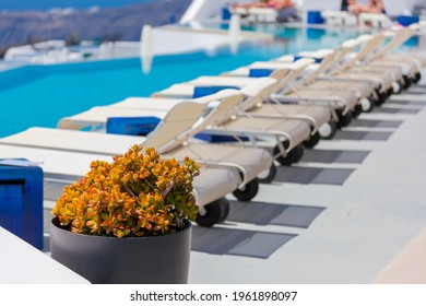 Greece Santorini island in Cyclades, traditional detail sights of colorful flowers with pots by pool and caldera sea in background