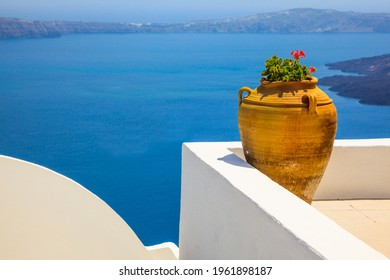 Greece Santorini island in Cyclades, traditional detail sights of colorful flowers with pots and caldera sea in background