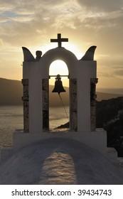 Greece. Santorini island. Oia village. Church bell in the rays of the yellow setting sun