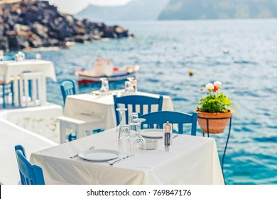 Greece, Santorini. Restaurant with served table in seafront of Aegean sea on Santorini Cyclades island with breathtaking, amazing and unbelievable view on the water and embankment of Oia Ia village.