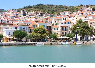 Greece, Skopelos, July 19 2017, summer landscape of Skopelos town seen from the sea with many people walking on the quay