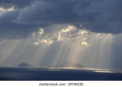 Greece. Sunbeams cutting stormy sky over islands near Santorini.