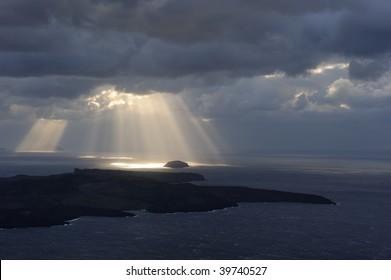 Greece. Sunbeams over islands near Santorini and volcano