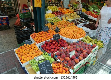 GREECE, THESSALONIKI, JUNE 10, 2013: People near shop counter with fresh fruits on the market place in Thessaloniki, Greece