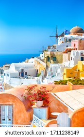 Greece Traveling. View of Greek Traditional Colorful Houses and Windmills of Oia or Ia at Santorini Island in Greece at Daytime. Vertical Shot