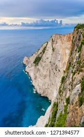 Greece, Zakynthos, Abrupt massive rock wall cliff in azure waters at navagio beach