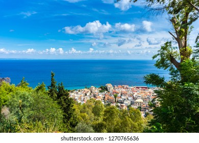 Greece, Zakynthos, Endless blue ocean and houses of zakynthos old town behind green trees