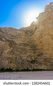 Greece, Zakynthos, Impressive abrupt chalk rock cliffs of navagio beach with sunlight