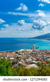 Greece, Zakynthos, Turquoise ocean water behind harbor and cityscape of zakynthos town from above