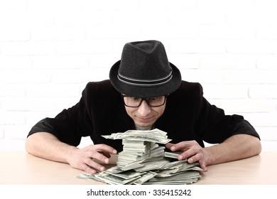 Greediness. emotional man in glasses holding bundles of money. Greed