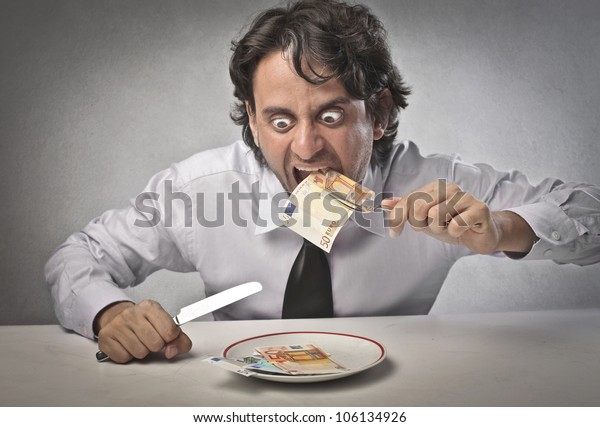 Greedy businessman eating banknotes from a dish