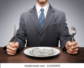 Greedy businessman eating banknotes symbolising consumerism.