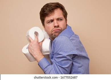 Greedy caucasian man holding several rolls of toiler paper on his hand hiding it from other people. Panic because of coronavirus situation.