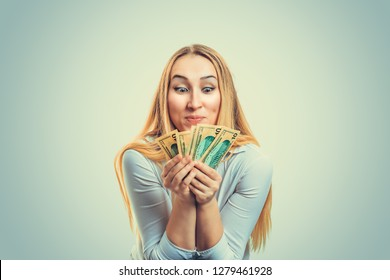 Greedy girl with currency American dollars money. Blond woman in white shirt holding heap of money and frowning in greediness looking at money. Negative human emotion face expression feeling reaction