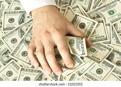 Greedy hand grabs money lot of dollars