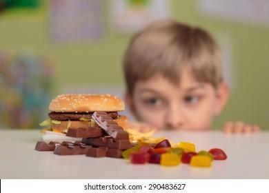 Greedy little boy looking at unhealthy tasty snacks