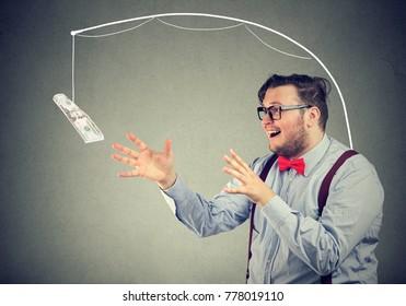 Greedy man chasing dollar bill on gray background.