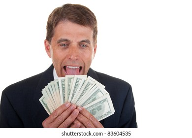 Greedy middle aged successful businessman licking his hard earned money.