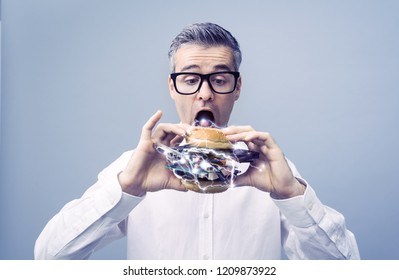 Greedy nerd IT technology enthusiast eating a sandwich filled with hardware and computer parts