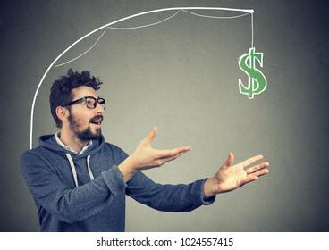 Greedy young man chasing dollar bill money on gray background.
