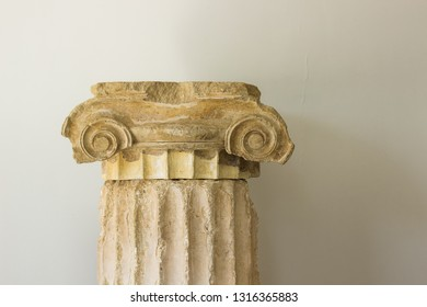 Greek antique column exhibit object on white wall background, museum sightseeing concept photography