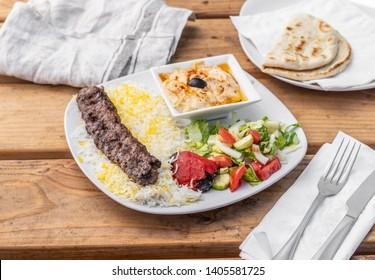 Greek beef kafta served with rice, hummus and a warm pita in a Mediterranean restaurant.