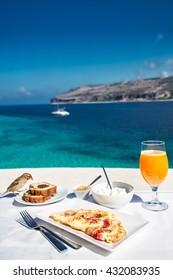 Greek breakfast with omelet and yogurt  against Mediterranean sea