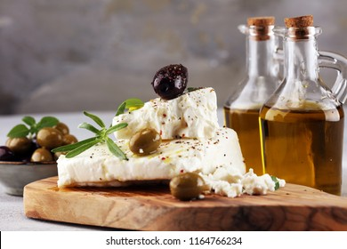 Greek cheese feta with herbs and olives on rustic table