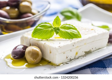 Greek cheese feta with olive oil olives and basil leaves.