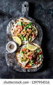 Greek chicken gyros flatbread on a rustic cutting board on a dark background, top view