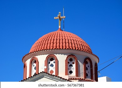 Greek church with a dome and cross in the town centre, Elounda, Crete, Greece, Europe.