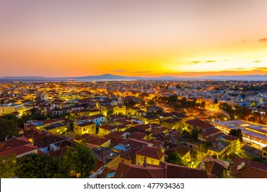 Greek city skyline in the evening after sunset with city lights in the foreground