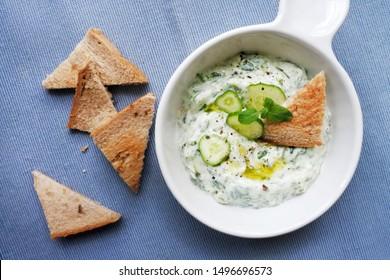 Greek Cucumber Yogurt Sauce Dip/ Tzatziki/ Creamy Greek Cucumber Salad with yogurt and mint. With whole wheat toast sliced bread.