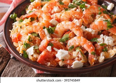 Greek cuisine: shrimp Saganaki with feta cheese and tomatoes close-up on a plate. horizontal