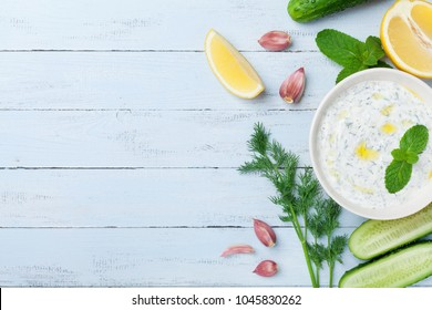 Greek dip sauce or dressing tzatziki from sour cream yogurt decorated with olive oil and mint on wooden table top view.