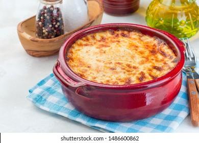 Greek dish moussaka made in traditional ceramic pot, horizontal