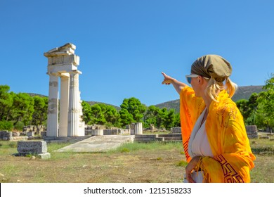 Greek dressed woman in indicates the ruins of Temple of Asklepieion, Epidaurus, Peloponnese, Greece. The Sanctuary of Asclepius is a famous heritage site.Mediterranean travel and tourism concept