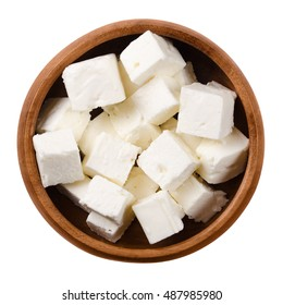 Greek Feta cheese cubes in a wooden bowl on white background. Cubes of a brined curd white cheese made in Greece from milk of sheeps and goats. Crumbly aged cheese with slightly grainy texture.