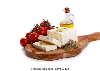 Greek feta cheese with oregano,olive oil and tomatoes on cutting board isolated over white