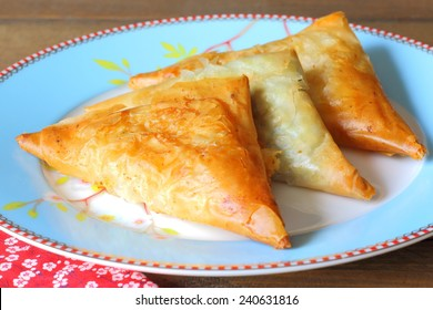 Greek feta cheese triangle pies called tiropitas or tiropitakias. They are made with phyllo pastry and filled with feta cheese and also spinach.