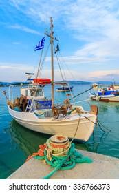 Greek fishing boat mooring in port at sunset time, Samos island, Greece