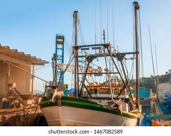 Greek fishing boats stays parked near sea pier.