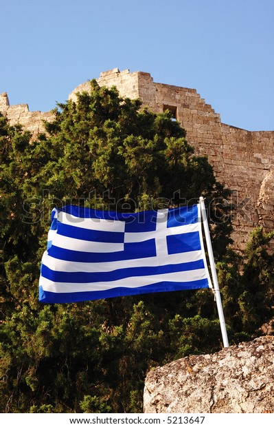 Greek flag; in the background the walls of Lindos Castle; Rhodes, Greece.