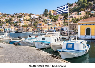 Greek flag, boats and colorful neoclassical houses in harbor town of Symi (Symi Island, Greece)