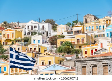 Greek flag and colorful neoclassical houses in harbor town of Symi (Symi Island, Greece)
