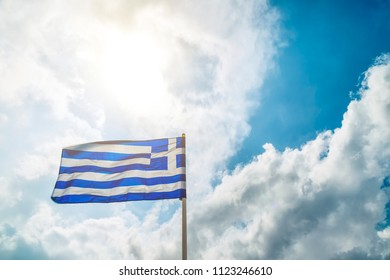 Greek flag fluttering in the wind on a background of blue sky with clouds and sun