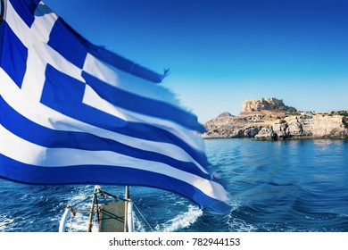 Greek flag and Lindos acropolis in background from boat deck (Rhodes, Greece)
