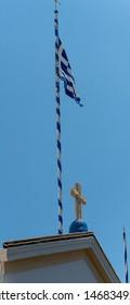The Greek flag on a flag pole above a Christian cross